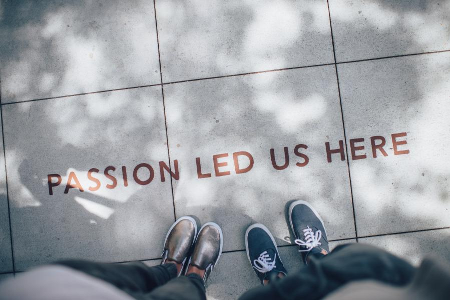 "View of two pairs of feet standing on a cement block that reads ""Passion led us here"""