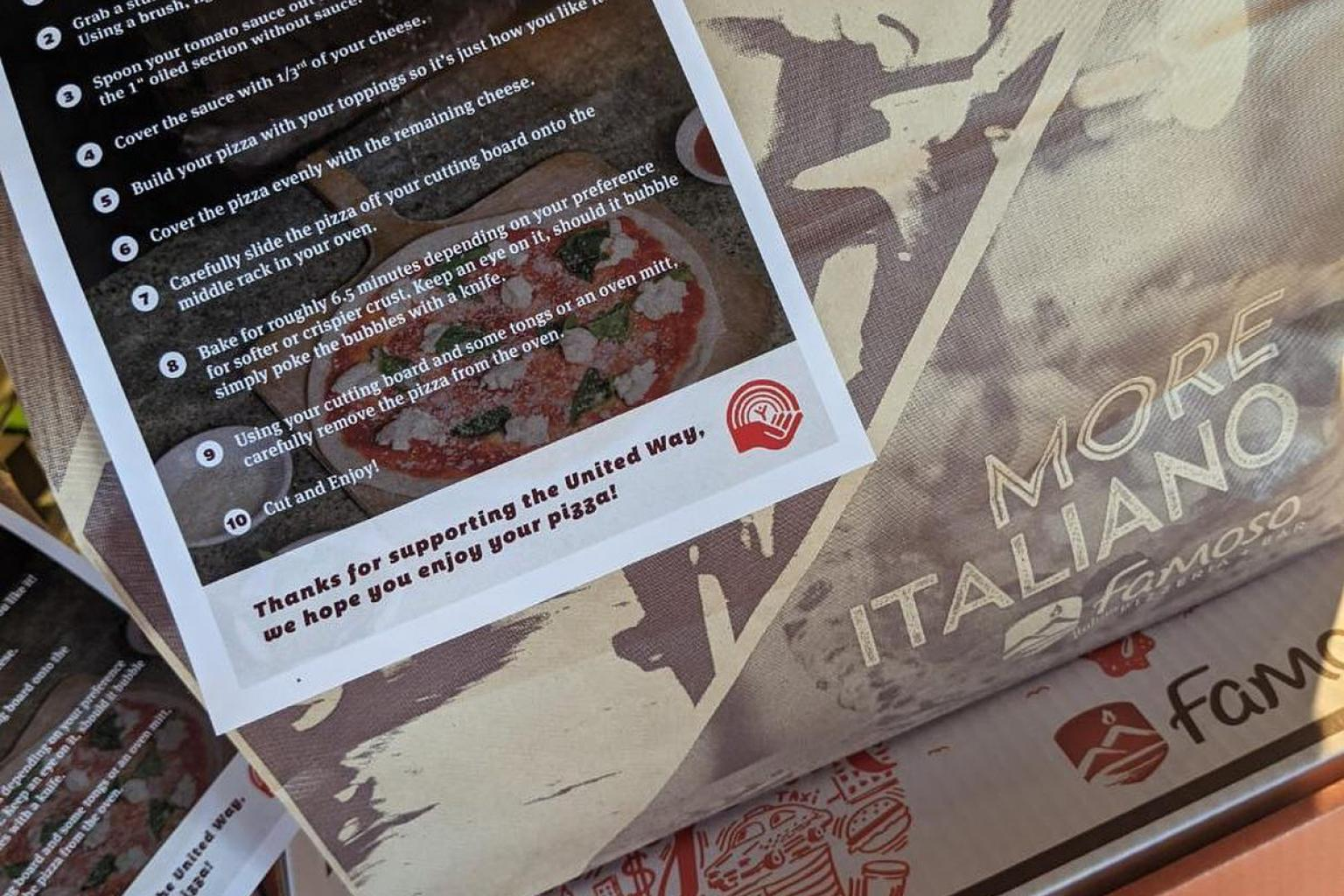 A stack of Famoso pizza boxes with a Take And Bake instructions sheet on top